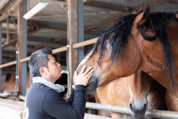 馬肉自然づくりドッグフードの肥育牧場の馬と鈴木田さん